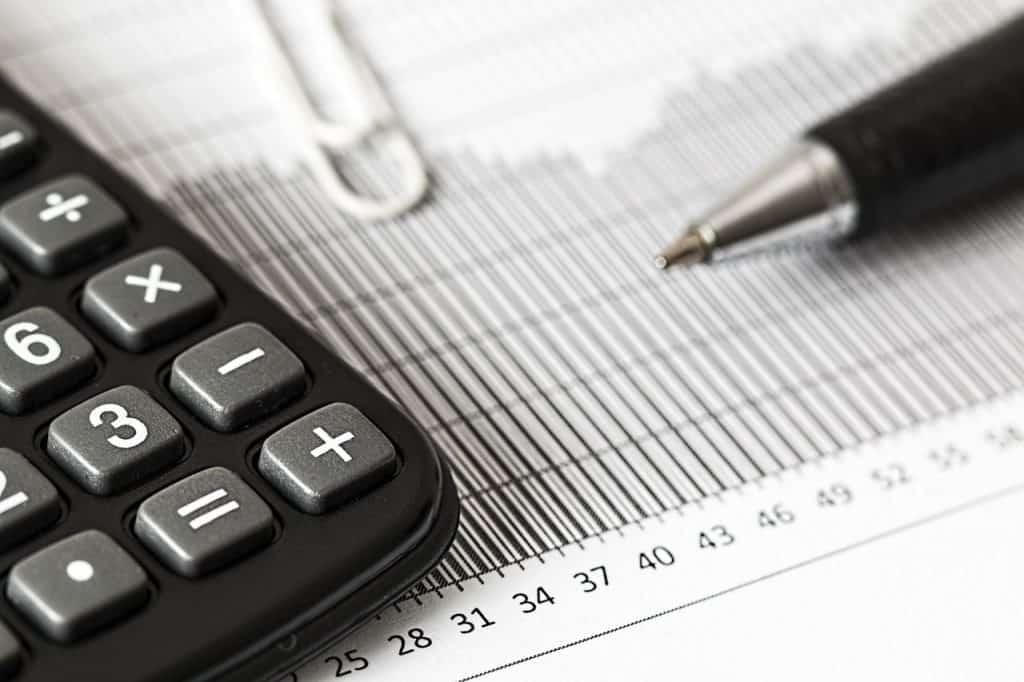 Taschenrechner und Stift auf einem Blatt mit Wochenzahlen Investitionsabzugsbetrag